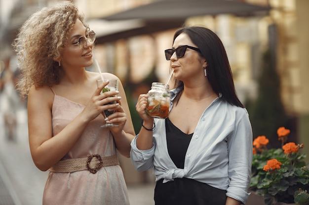 Mulheres elegantes tomam coquetéis em cidade de verão