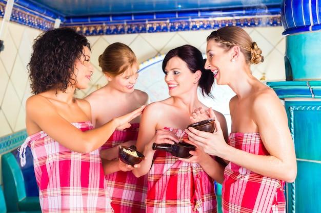 Mulheres em banho de vapor hammam com peeling de bem-estar