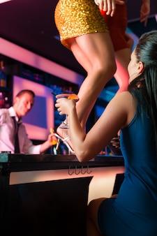 Mulheres em bar ou clube estão dançando em cima da mesa