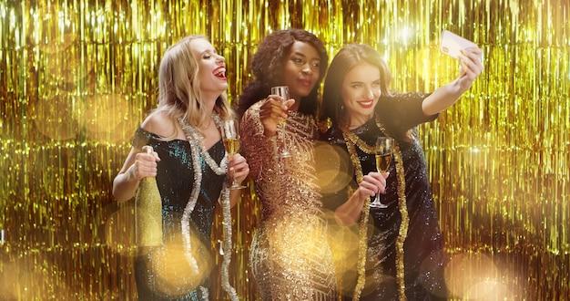 Mulheres em belos vestidos e champanhe tomando selfie