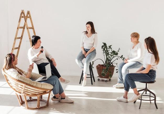 Mulheres em camisas brancas, tendo uma conferência