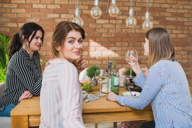 Mulheres, em, camisas coloridas, sentando, tabela