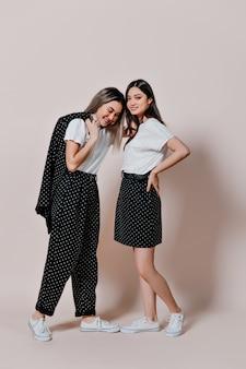 Mulheres em camisetas brancas e trajes de bolinhas pretas posando em uma parede bege