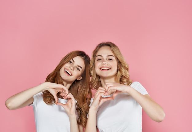 Mulheres em camisetas brancas ficam ao lado de emoções amizade fundo rosa