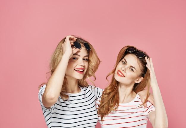 Mulheres em camisetas listradas usando óculos escuros fundo rosa