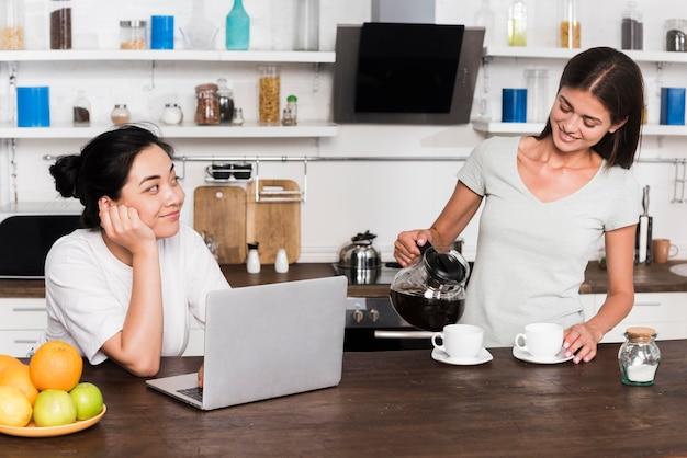 Mulheres em casa na cozinha com café e laptop