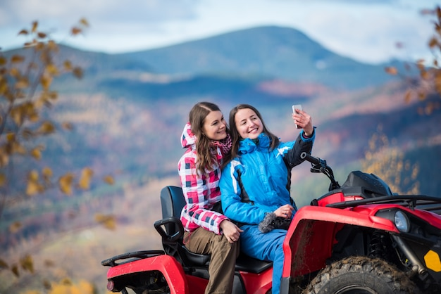 Mulheres em casacos de inverno na moto quad vermelho
