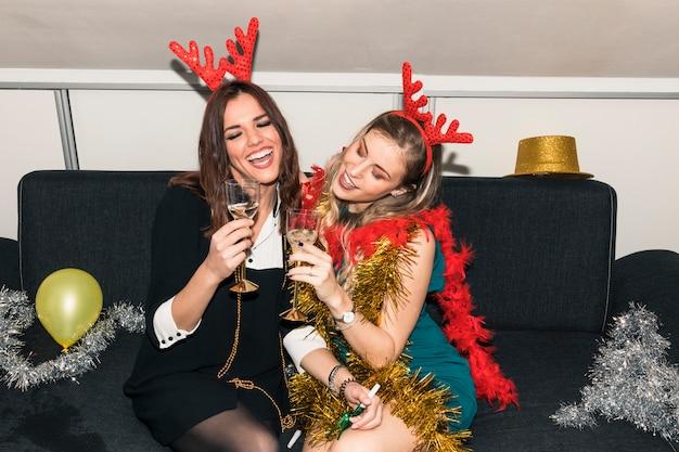 Mulheres em chifres de veado sentado com taças de champanhe