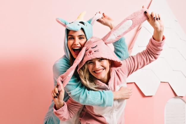 Mulheres em êxtase em kigurumi brincando juntas
