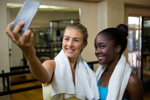 Mulheres em forma bonita tirando selfie no celular após o treino