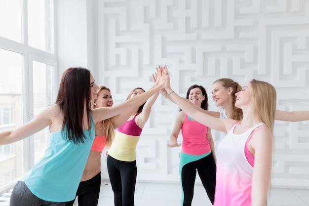Mulheres em forma esportiva usando roupas esportivas, dando cinco umas às outras