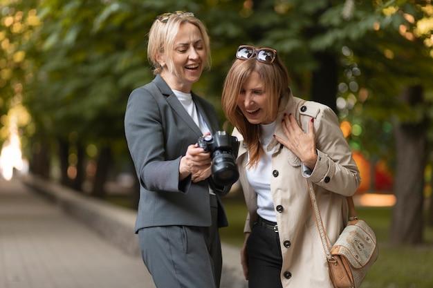 Mulheres em fotos médias com câmera fotográfica