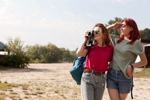 Mulheres em meados de fotos tirando fotos na natureza