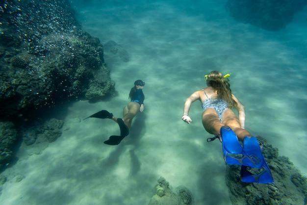 Mulheres em mergulho livre com nadadeiras subaquáticas
