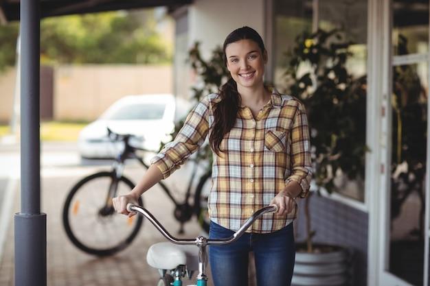 Mulheres em pé com bicicleta fora do café