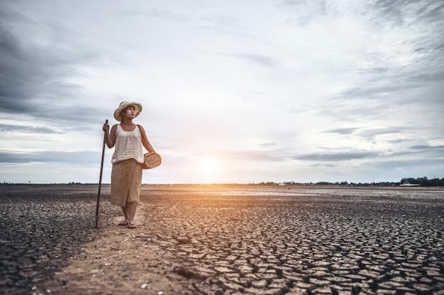 Mulheres em pé em solo seco e equipamentos de pesca, aquecimento global e crise da água
