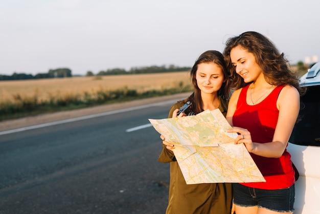 Mulheres em pé perto de carro branco e olhando para o mapa