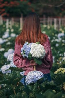 Mulheres em pé segurando flores de hortênsia