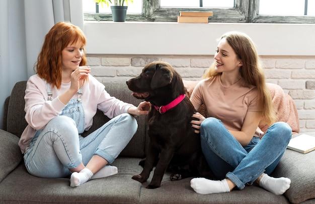 Mulheres em plena cena e cachorro no sofá
