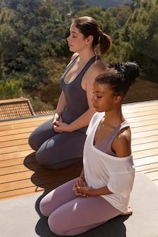 Mulheres em pleno tiro meditando no tapete