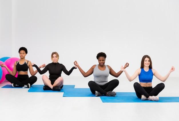 Mulheres em posição de ioga na aula de fitness