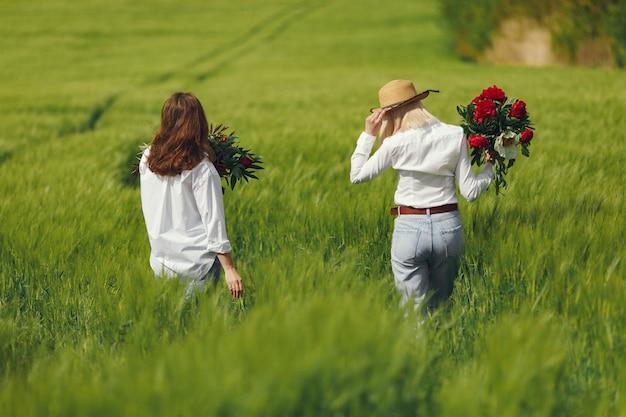 Mulheres em roupas elegantes, de pé em um campo de verão