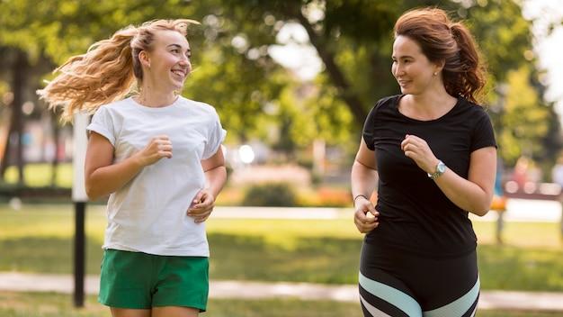 Mulheres em roupas esportivas correndo juntas no parque