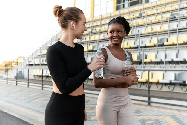 Mulheres em roupas esportivas fazendo uma pausa do treino