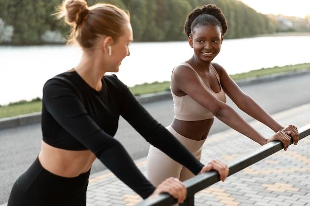 Mulheres em roupas esportivas malhando ao ar livre