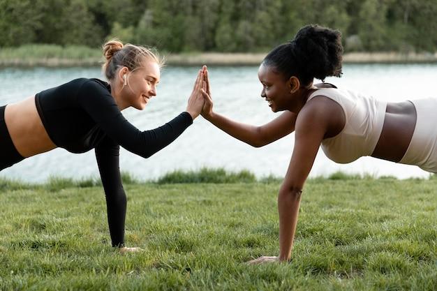 Mulheres em roupas esportivas malhando ao ar livre Foto gratuita