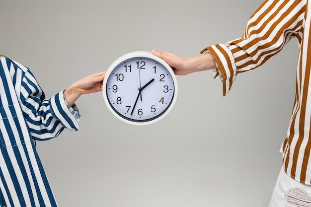 Mulheres em roupas listradas de tamanho grande carregando um relógio de parede liso entre elas com as duas mãos
