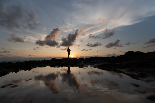 Mulheres em silhueta com lindo céu nublado na hora do pôr do sol e lagoa de reflexão / textura de fundo / céu natural