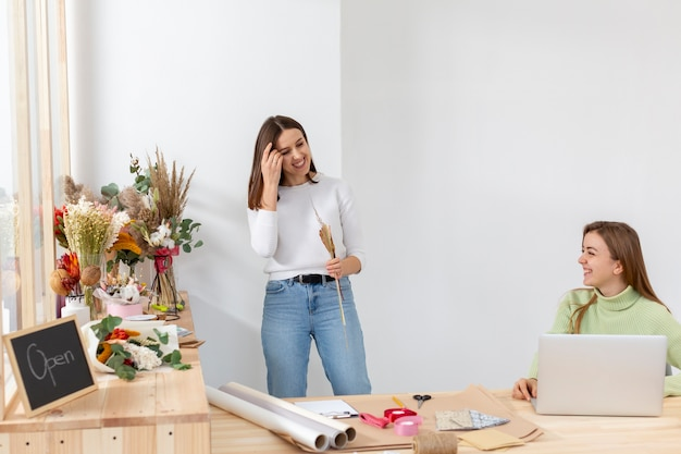 Mulheres em sua loja de flores sendo felizes