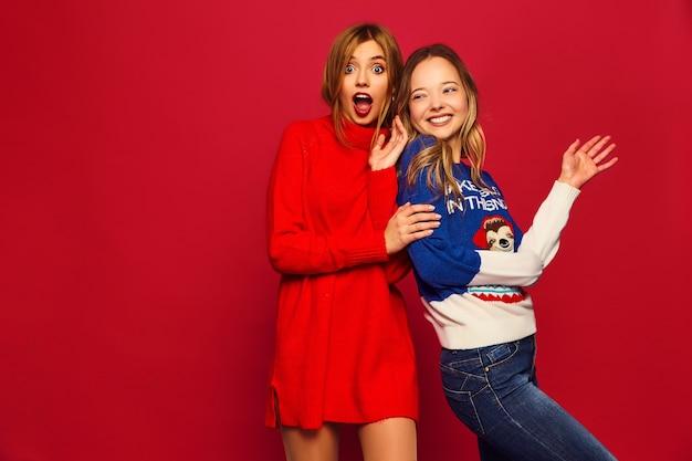 Mulheres em suéteres quentes elegantes de inverno na parede vermelha