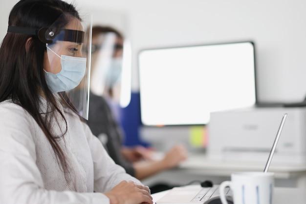 Mulheres em telas de proteção trabalhando em laptops no escritório