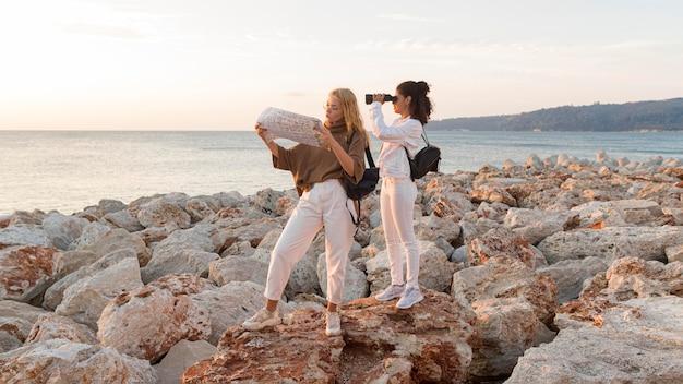 Mulheres em tiro completo com mapa e binóculos