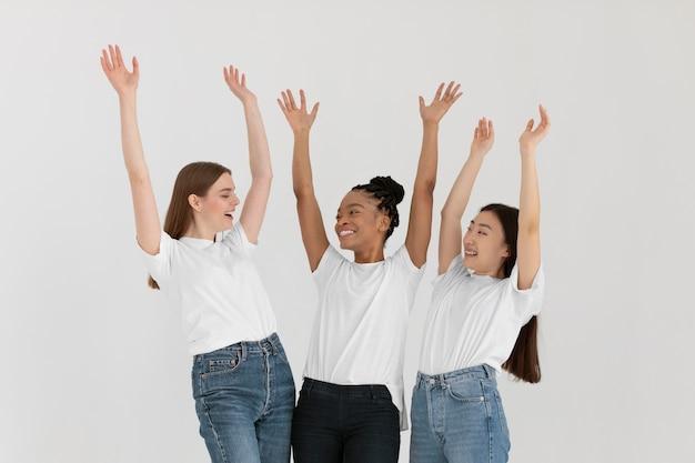 Mulheres em tiro médio com as mãos para cima