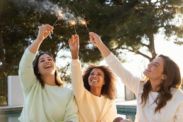 Mulheres em tiro médio com fogos de artifício