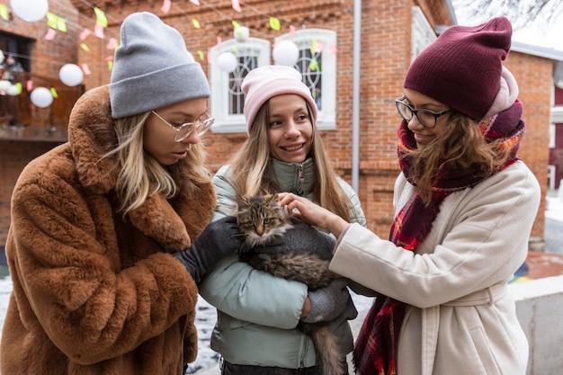 Mulheres em tiro médio com gato fofo