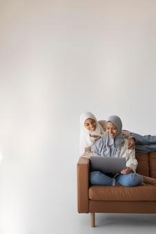 Mulheres em tiro médio com laptop no sofá
