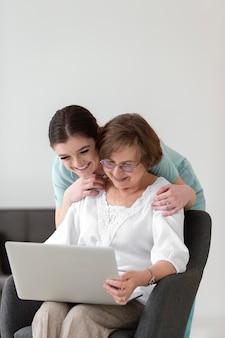 Mulheres em tiro médio com laptop