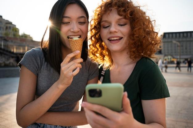 Mulheres em tiro médio com telefone