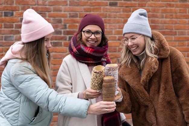 Mulheres em tiro médio segurando bolos de chaminé