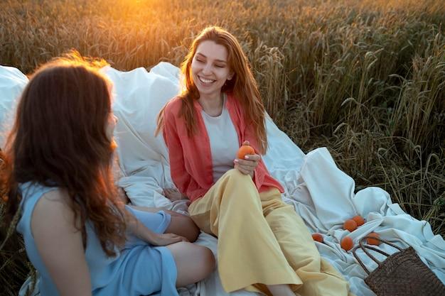 Mulheres em tiro médio sentadas ao ar livre