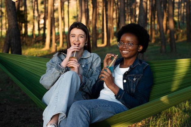 Mulheres em tiro médio sentadas em redes