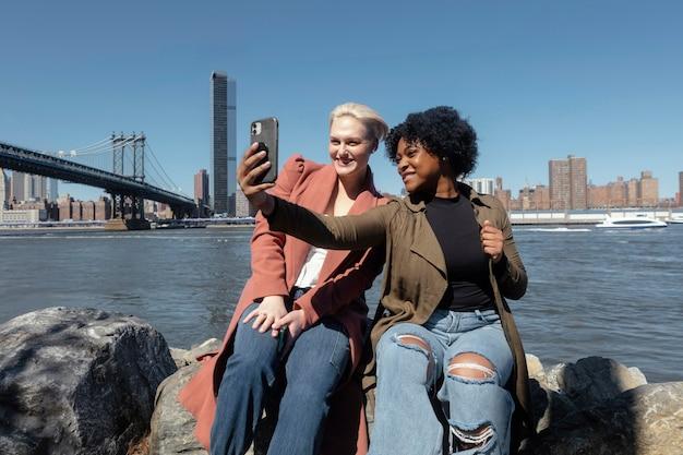 Mulheres em tiro médio tirando selfie em nova york