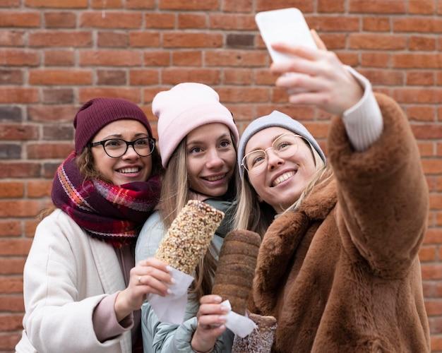 Mulheres em tiro médio tirando selfies