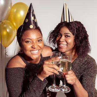 Mulheres em tiro médio usando chapéus de festa e brindando