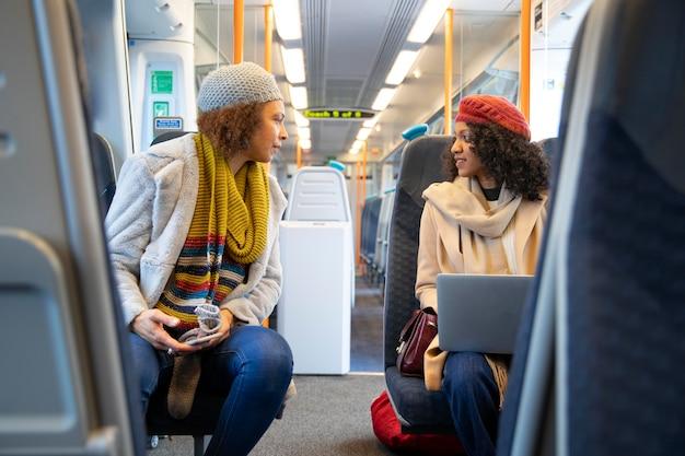 Mulheres em tiro médio viajando de trem