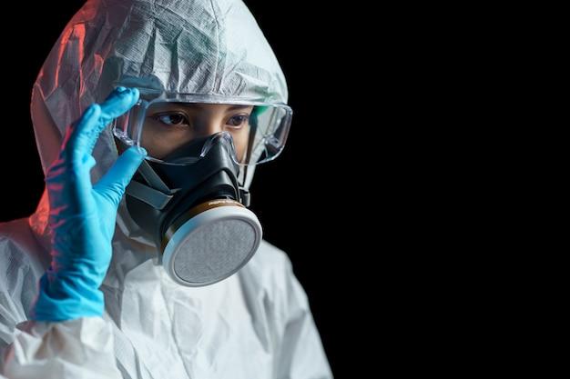 Mulheres em traje de proteção hazmat, máscara respiratória e óculos olhando em vazio